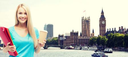 educación, escuela, estudio en el extranjero, bebidas y concepto de la gente - la muchacha del estudiante con las carpetas y taza de café sobre fondo de la ciudad de Londres sonriendo
