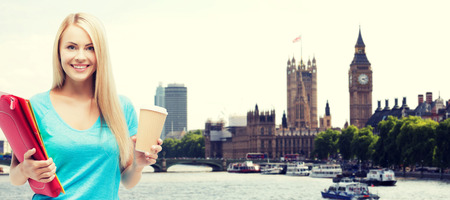 education, school, study abroad, drinks and people concept - smiling student girl with folders and cup of coffee over london city background Zdjęcie Seryjne