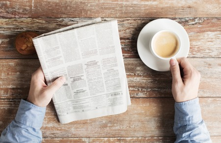 coffee table: business, information, people and mass media concept - close up of male hands with newspaper, muffin and coffee cup on table