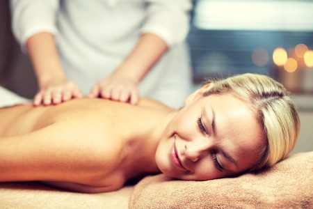 Menschen, Schönheit, Spa, gesunden Lebensstil und Entspannung Konzept - Nahaufnahme der schönen jungen Frau mit geschlossenen Augen liegt und Handmassage in Spa-