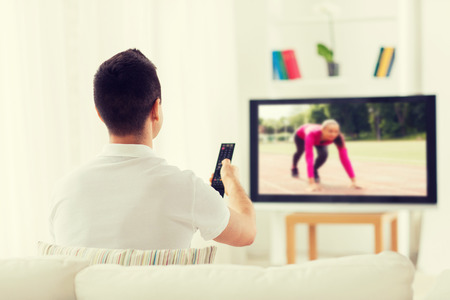 leisure, technology, mass media and people concept - man with remote control watching sport channel on tv at home from back Stock Photo