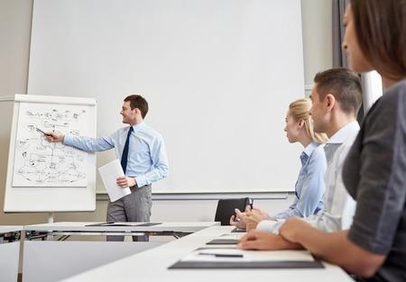 affaires, la planification, les gens et concept de travail d'équipe - groupe de gens d'affaires sourire réunion sur présentation dans le bureau Banque d'images