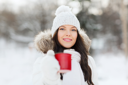 hot drink: people, season, drinks and leisure concept - happy young woman with tea cup outdoors in winter