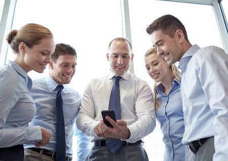 happy workers: business, teamwork, people and technology concept - business team looking to smartphone in office Stock Photo