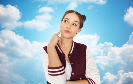 blue sky thinking: people and teens concept - happy pretty teenage girl thinking over blue sky and clouds background