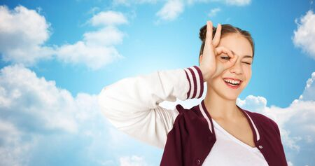 clouds making: people and teens concept - happy smiling pretty teenage girl making face and having fun over blue sky and clouds background