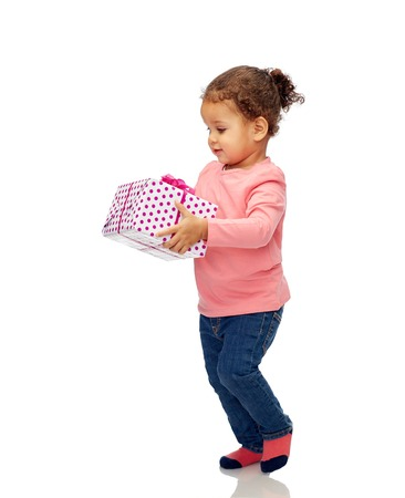 african child: childhood, fashion, birthday, holidays and people concept - beautiful little african american baby girl walking with gift box Stock Photo