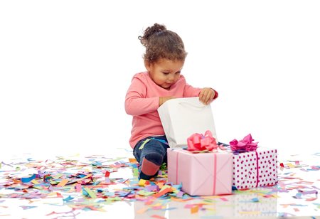 children birthday: childhood, birthday, party, holidays and people concept - happy smiling little african american baby girl with gift boxes and confetti playing with shopping bag sitting on floor