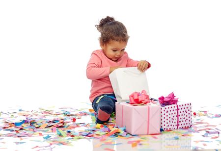afroamericanas: infantiles, cumpleaños, fiesta, vacaciones y concepto de la gente - pequeño bebé feliz del afroamericano con cajas de regalo y confeti jugando con bolsa de compras sentado en el suelo