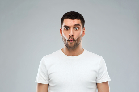 silly face: expression, fun and people concept - man with funny fish-face over gray background Stock Photo