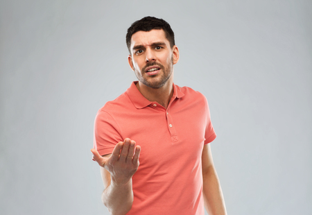 mockery: emotion, gesture, argue and people concept - arguing angry man proving something over gray Stock Photo