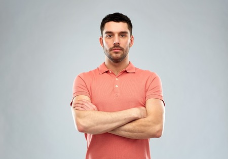 people concept - serious young man in polo t-shirt with crossed arms over gray background Stockfoto