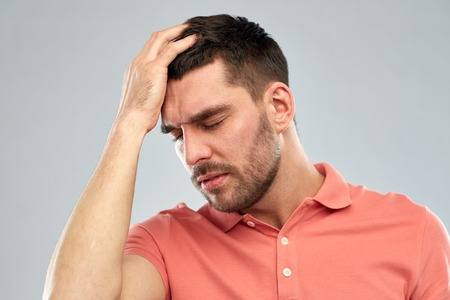head ache: people, crisis, emotions and stress concept - unhappy man suffering from head ache over gray background