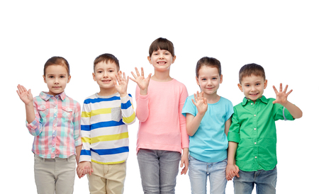 waving: childhood, fashion, friendship and people concept - group of happy smiling little children holding hands