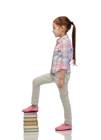childhood, school, education and people concept - happy little girl stepping on book pile 免版税图像