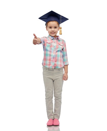 pre approval: childhood, school, education, learning and people concept - happy girl with in bachelor hat or mortarboard showing thumbs up Stock Photo