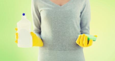manos limpias: las personas, las tareas del hogar, lavado y limpieza concepto - cerca de la mujer que sostiene una esponja y limpiador de botella sobre fondo verde