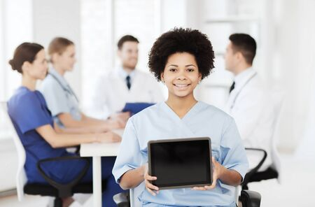 medics: clinic, profession, people and medicine concept - happy female doctor or nurse showing tablet pc computer blank screen over group of medics meeting at hospital Stock Photo