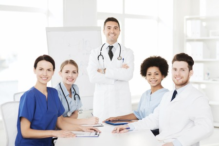 medical education: hospital, profession, medical education, people and medicine concept - group of happy doctors meeting on presentation or conference at hospital Stock Photo