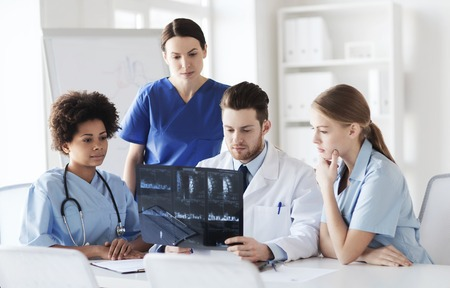 medics: radiology, people and medicine concept - group of doctors looking to and discussing x-ray image at hospital Stock Photo