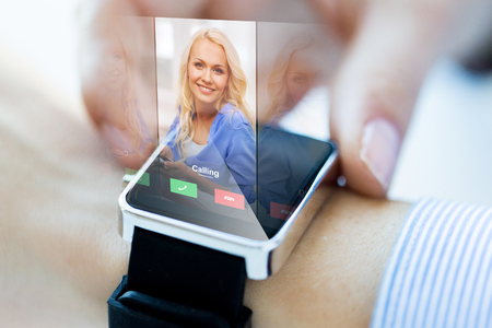 incoming: business, communication, technology and people concept - close up of woman hands setting smart watch with incoming call Stock Photo