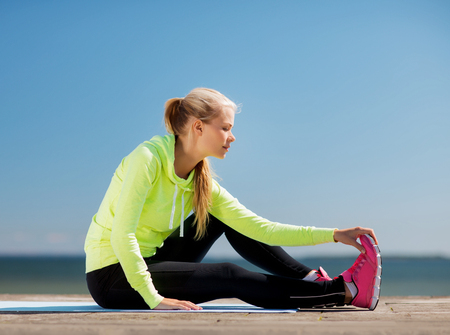 sports: sport and lifestyle concept - woman doing sports outdoors Stock Photo