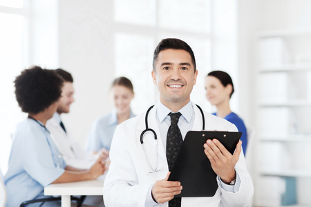 medics: clinic, profession, people and medicine concept - happy male doctor with clipboard over group of medics meeting at hospital Stock Photo