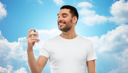 perfumery concept: perfumery, beauty and people concept - happy smiling young man with male perfume over blue sky and clouds background Stock Photo
