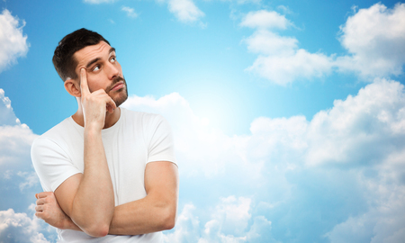 blue sky thinking: doubt, expression and people concept - man thinking over blue sky and clouds background