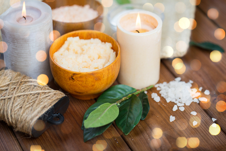 natural therapy: beauty, spa, therapy and natural cosmetics concept - close up of body scrub, salt and candles on wood