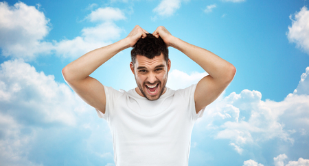 paranoia: emotions, stress, madness and people concept - crazy shouting man rending ones hair in t-shirt over blue sky and clouds background