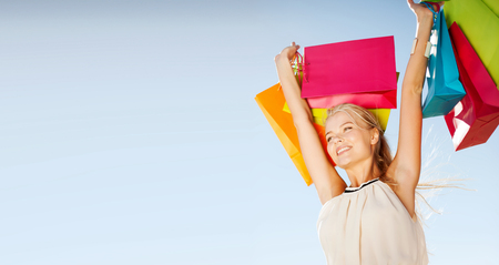 women smiling: shopping and tourism concept - woman with shopping bags Stock Photo