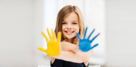 school classroom: education, school, art and painitng concept - little student girl showing painted hands at school