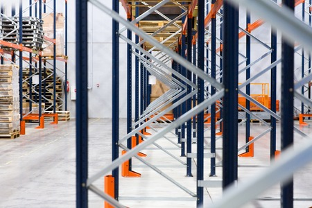 logistics: logistic, storage, shipment, industry and manufacturing concept - warehouse shelves or constructions with cargo Stock Photo
