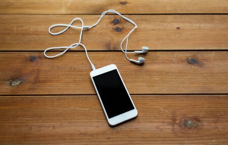 podcast: technology, music, gadget and object concept - close up of white smartphone and earphones on wooden surface with copy space