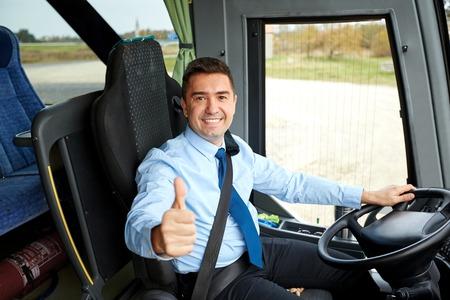 Trasporti, turismo, viaggio su strada e la gente concetto - autista felice di guida degli autobus interurbani e pollici altezza del manto nevoso Archivio Fotografico - 59097620