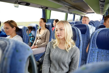 transporte, turismo, viaje por carretera y las personas concepto - mujer joven con el grupo de pasajeros o turistas en viajes de autobús Foto de archivo