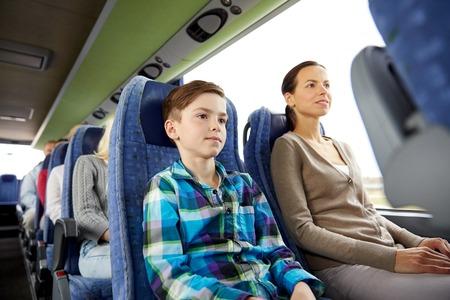 Voyage, tourisme, famille, de la technologie et les gens concept - mère heureuse et son fils à cheval dans le bus de Voyage