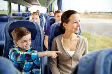 travel, tourism, family, technology and people concept - happy mother and son riding in travel bus Stock Photo