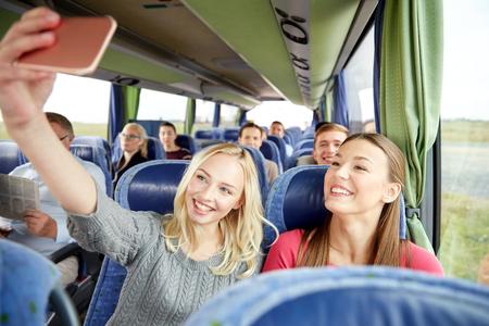 transporte, turismo, viaje por carretera y el concepto de las personas - mujeres jóvenes felices o amigos en autobús de viaje que tenga autofoto por teléfono inteligente