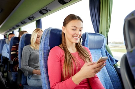 travel woman: transport, tourism, road trip and people concept - happy young woman sitting in travel bus with smartphone