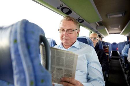 buses: transport, tourism, trip and people concept - senior man reading newspaper in travel bus