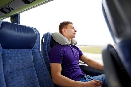 vervoer, toerisme, weg reis, rust en mensen concept - gelukkig jonge man slapen in de bus reizen met opblaasbaar kussen Stockfoto