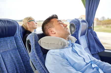 vervoer, toerisme, rust, comfort en de mensen concept - man slapen in de bus reizen met cervicale nek opblaasbaar kussen