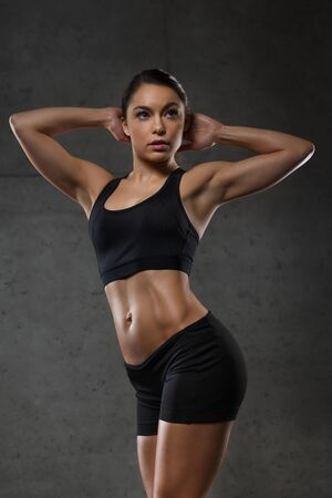 showing muscles: sport, fitness, bodybuilding, weightlifting and people concept - young woman posing and showing muscles in gym