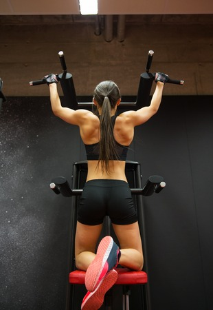 pullups: sport, fitness, lifestyle and people concept - woman exercising and doing pull-ups in gym from back Stock Photo