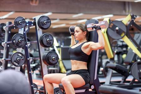 deporte, fitness, culturismo, levantamiento de pesas y el concepto de la gente - mujer joven con mancuernas flexionando los músculos en el gimnasio de la parte posterior