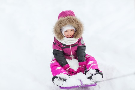sledding: childhood, sledding, fashion, season and people concept - happy little kid on sled outdoors in winter