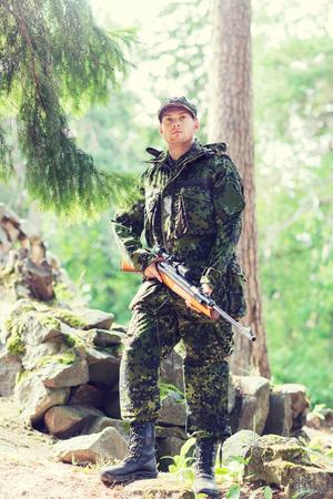 cazador: la caza, la guerra, el ejército y el pueblo concepto - joven soldado, guardabosques o cazador con el arma en bosque