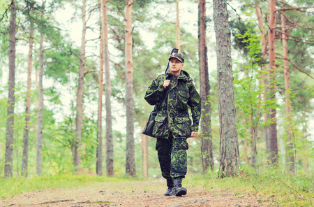 ranger: hunting, war, army and people concept - young soldier, ranger or hunter with gun walking in forest